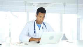 Афро-американский доктор печатая на компьтер-книжке в больнице стоковое фото