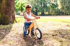 Афро-американский или латинский велосипед езды мальчика в парке стоковые изображения rf