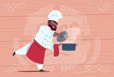 Афро-американский кашевар шеф-повара держа кастрюльку с вождем шаржа горячего супа усмехаясь в белой форме ресторана над деревянн бесплатная иллюстрация