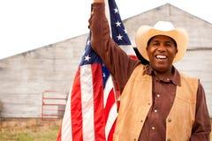 Афро-американский ковбой держа американский флаг Стоковое Фото