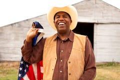 Афро-американский ковбой держа американский флаг Стоковое Изображение RF