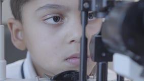 Афро-американский мальчик делая тест глаза с optometrist смотря машину тест видеоматериал