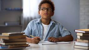 Афро-американский мальчик думая на эссе школы, умный ребенк делая домашнюю работу, образование стоковое изображение