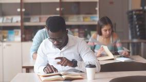 Афро-американский мужской коллеж studen подготовка для экзаменов в библиотеке видеоматериал