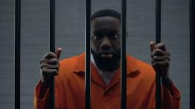 Афро-американский мужской пленник держа бары и смотря к камере, заточению видеоматериал