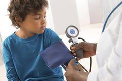 Афро-американский доктор женщины принимая кровяное давление child's стоковые изображения rf