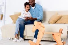 Афро-американский отец и дочь наблюдая что-то на таблетке с тряся лошадью Стоковая Фотография