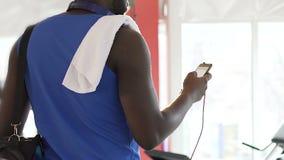 Афро-американский парень стоя в спортзале, перечисляя экран мобильного телефона, отделка сток-видео
