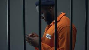 Афро-американский пленник используя телефон в клетке, коррупции в тюрьмах, запрете акции видеоматериалы