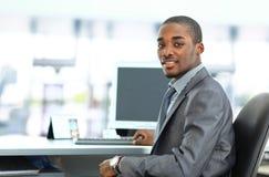 Афро-американский предприниматель показывая компьтер-книжку компьютера в офисе Стоковые Изображения RF