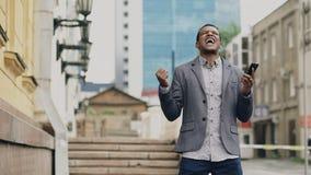 Афро-американский радостный бизнесмен счастливый после говорить телефон о его новой карьере Стоковое Изображение