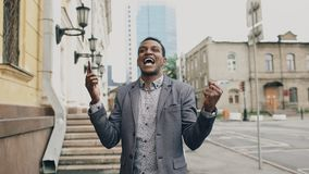 Афро-американский радостный бизнесмен счастливый после говорить телефон о его новой карьере Стоковые Фото