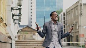 Афро-американский радостный бизнесмен счастливый после говорить телефон о его новой карьере Стоковое Изображение RF