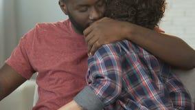 Афро-американский супруг обнимая его милую жену, ослабляя совместно дома, влюбленность акции видеоматериалы