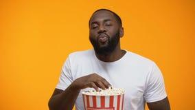 Афро-американский человек есть попкорн и наблюдая интересное серийное, конец-вверх акции видеоматериалы