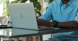 Афро-американский человек используя ноутбук в кафе деля идеи дела сток-видео