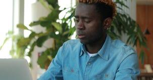 Афро-американский человек используя ноутбук в кафе деля идеи дела видеоматериал
