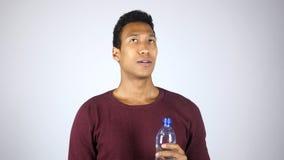 Афро-американский человек ослабляя после питьевой воды от бутылки, чувствуя Satisfie Стоковое Изображение RF
