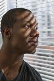 Афро-американский человек смотря вне окно и усмехаться, вертикальные стоковое изображение