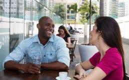 Афро-американский человек flirting с кавказской женщиной на ресторане Стоковая Фотография RF