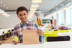 Афро-американский школьник с сумкой яблока и обеда стоковые изображения