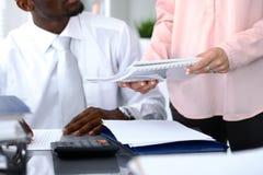 Афро-американский bookkeeper или финансовый контролер делая отчет, высчитывая или проверяя баланс Внутреннее Revenu Стоковые Изображения RF