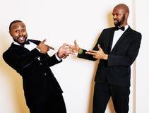2 афро-американских бизнесмена в черных костюмах эмоциональный представлять, показывающ жестами, усмехаясь нося бабочки, люди обр Стоковые Изображения