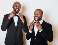 2 афро-американских бизнесмена в черных костюмах эмоциональный представлять, показывающ жестами, усмехаясь нося бабочки Стоковое фото RF