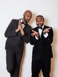 2 афро-американских бизнесмена в черных костюмах эмоциональный представлять, показывающ жестами, усмехаясь нося бабочки Стоковое Изображение