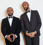 2 афро-американских бизнесмена в черных костюмах эмоциональный представлять, показывающ жестами, усмехаясь нося бабочки Стоковые Фото