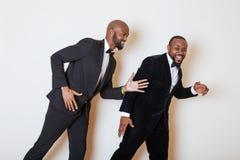 2 афро-американских бизнесмена в черных костюмах эмоциональный представлять, показывающ жестами, усмехаясь нося бабочки Стоковая Фотография