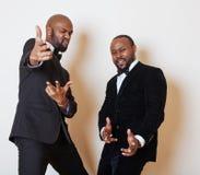 2 афро-американских бизнесмена в черных костюмах эмоциональный представлять, показывающ жестами, усмехаясь нося бабочки Стоковое Фото