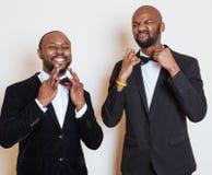 2 афро-американских бизнесмена в черных костюмах эмоциональный представлять, показывающ жестами, усмехаясь нося бабочки Стоковые Фотографии RF