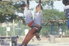2 Афро-американских дет играя на оборудовании спортивной площадки в Чикаго, IL Стоковое Изображение