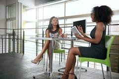 2 Афро-американских женщины обсуждая идеи используя Стоковая Фотография RF