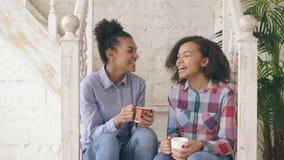 2 Афро-американских курчавых sistres девушек сидя на лестницах имеют потеху смеясь над и беседуя совместно дома сток-видео