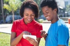2 Афро-американских молодых взрослого смотря телефон Стоковое Изображение