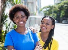 2 Афро-американских подруги смеясь над в городе Стоковое Фото