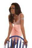 Афро-американское платье пинка женщины за голубым стулом стоковые изображения