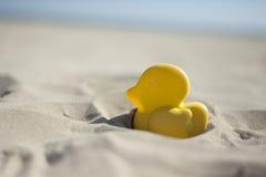 Аффикс игрушки пляжа утки лета желтый в сухом песке Селективный fo Стоковая Фотография RF