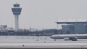 Аэробус Air China ездя на такси в авиапорте Мюнхена, снеге