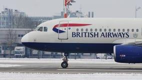 Аэробус A320-200 British Airways ездя на такси на авиапорте Мюнхена, снеге видеоматериал