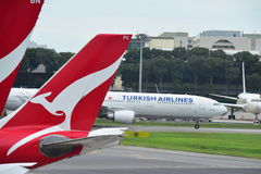Аэробус A330 Turkish Airlines ездя на такси за воздушными судн Qantas на авиапорте Changi Стоковое Изображение RF