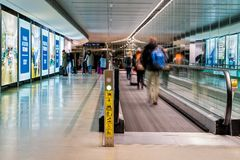 Аэропорт января 2019 Дублина †Дублина, Ирландии «, люди спеша для их полетов, длинный коридор с двигая дорожкой, нерезкостью дв стоковые изображения