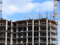Аэрофотоснимок неузнаваемого гражданского инженера без стороны, наблюдая работу построителей крыши на строительной площадке стоковые фото