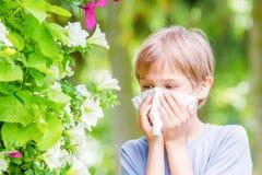 аллергически Мальчик дует его нос около дерева в цветени стоковое изображение