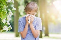 аллергически Мальчик дует его нос около дерева в цветени стоковое изображение rf