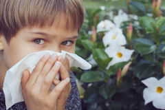 аллергически Ребенк дует его цветки носа близко blossoming стоковое фото rf