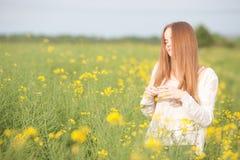 Аллергия цветня, девушка чихая в поле рапса цветков Стоковое Изображение RF