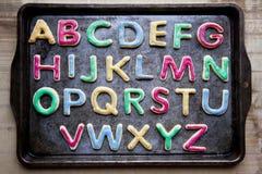 Алфавит в украшенных красочных печеньях на подносе выпечки, горизонтальном Стоковые Фотографии RF